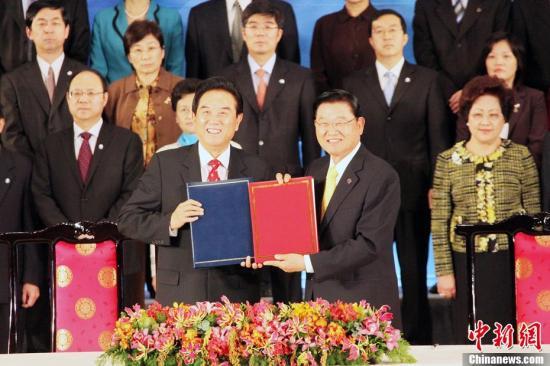 资料图:2010年12月21日下午,海协会会长陈云林与海基会董事长江丙坤在台北签署了《海峡两岸医药卫生合作协议》。这是两会自2008年恢复制度化协商以来签署的第15个两岸合作协议。图为陈云林与江丙坤在签署协议后互换文本。中新社记者 黄少华 摄
