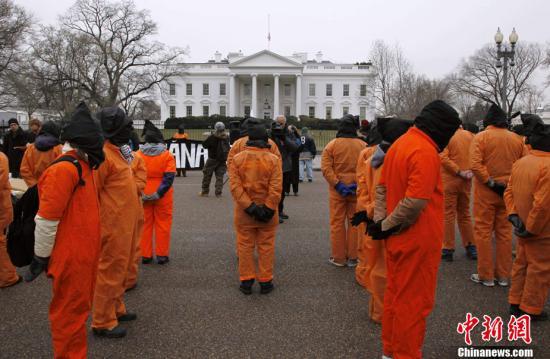 资料图:关塔那摩监狱建立9周年纪念日当天,美国华盛顿,示威者穿着橙色的囚服游行,要求关闭关塔那摩监狱。。
