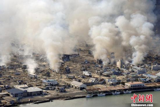资料图:北京时间2011年3月11日13点46分,日本本州岛附近海域发生里氏9.0级地震,震中位于宫城县以东太平洋海域,图为12日,遭受地震袭击的岩手县山田镇冒起滚滚白烟。