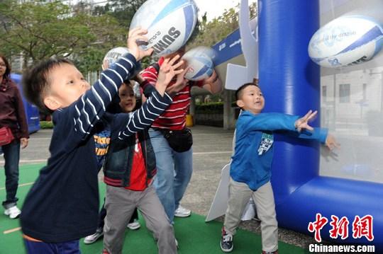 """3月18日,一班香港橄榄球队球星出席在遮打花园的""""榄球路演""""活动,许多市民纷请球星签名、拍照,更有儿童在球星鼓励下甩榄球显身手。 中新社发 郑祚声 摄"""