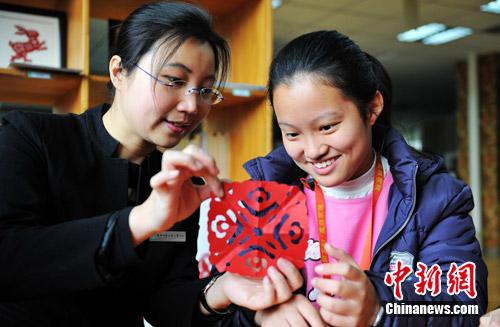 """3月18日,""""2011海峡两岸少年儿童科技嘉年华""""在四川成都启动。图为成都老师正在教台湾孩子学习民俗剪纸。中新社发 刘忠俊 摄"""