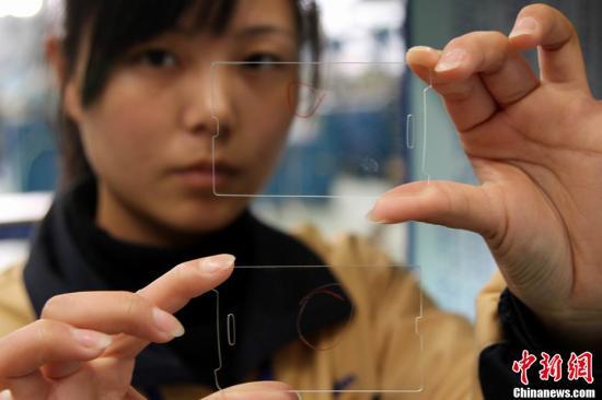 4月8日,在位于江西南昌经济开发区的南昌欧菲光科技有限公司车间内,技术工人正在对触摸屏强化面板进行打磨、抛光、检测等工序。据介绍,目前南昌正形成以欧菲光电子为代表的一批战略性新兴产业。图为用来供应手机的触摸屏强化面板。刘占昆 摄