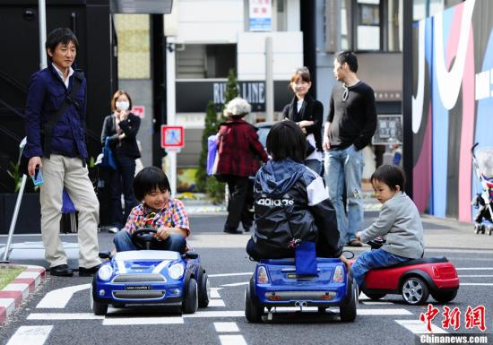 4月17日下午,几名日本儿童在家人的陪伴下在东京银座的汽车销售店外乘坐玩具电动车。/p中新社发 侯宇 摄