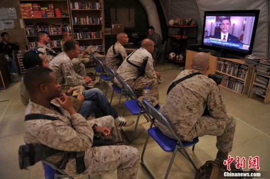 """美国总统奥巴马在当地时间2011年5月1日发表全国电视演讲,宣布""""基地""""组织领导人奥萨马•本•拉登已被打死。图为驻阿美军某团士兵关注奥巴马演讲的电视新闻。"""