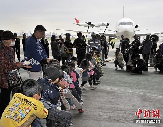当地时间5月5日,日本东京羽田机场,日本小姐选美佳丽与小学生等共约200人拉动重达90吨重的空客300型飞机。这是为庆祝日本儿童日而举行的活动。