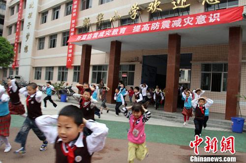"""原料图:重庆一幼学举走""""地震答急稀奇""""演练。图为孩子们跑出教学楼。阮守军 摄"""