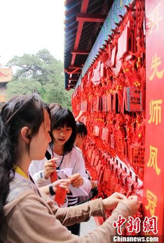 资料图为台湾学生在孔庙大成殿前悬挂许愿牌,祈福自己升学顺利。中新社发 李欣 摄