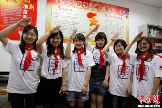 资料图 6月1日,上海一群外企女白领回到校园,带上红领巾重温儿童节。时下,上海成年人流行玩童年游戏、吃童年零食,以舒缓压力。红领巾、海魂衫、三道杠成为这几天最为热销的节日商品。汤彦俊 摄
