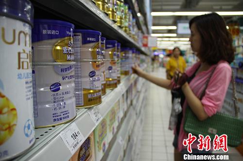 湖南长沙某超市内一名市民挑选进口奶粉(资料图)。发 杨华峰 摄