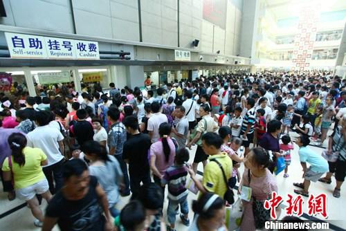 """7月12日,湖南省儿童医院门诊楼大厅内等候排队挂号、缴费的患者扎""""堆""""。刘柱 摄"""