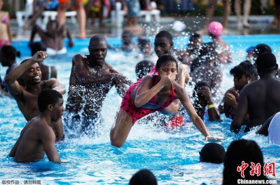 资料图:美国民众在游泳池内嬉水避暑。