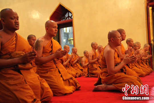 7月15日,是泰国三宝佛节。曼谷岱密寺当晚举行三宝佛节法会,图为诵经的僧侣们。发 余显伦 摄