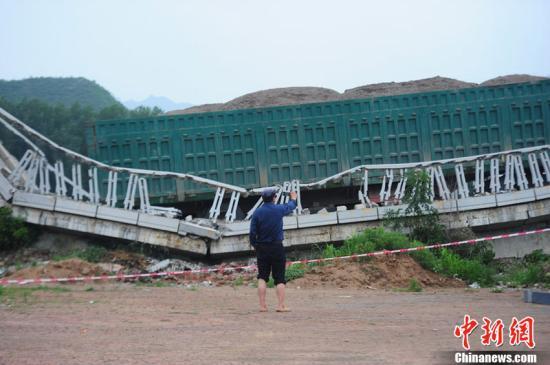 2011年7月19日零时40分,一辆重达160吨的严重超载沙石车,通过怀柔区宝山寺白河桥第一孔时发生桥梁坍塌,目前4孔全部坍塌,无人员伤亡。白河桥始建于1987年。根据《超限运输车辆行驶公路管理规定》(交通运输部2000年第2号令),货车车货总重超过46吨不允许擅自上路,而该车已经超过160吨,属于严重超载非法上路。潘之望 摄 图片来源:CFP视觉中国