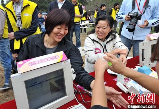 """10月25日,中国""""骨质疏松关爱大使""""、女排名将郎平(左)正在接受骨密度测试。为防治骨质疏松,中华医学会骨质疏松与骨矿盐疾病委员会与辉瑞制药当天联合启动""""千人健康走,预防骨松关爱行""""大型健身义诊活动,并在全国40个城市陆续展开。中新社发 曾利明 摄"""