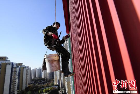 """11月9日,一名外墙清洗工人在北京某住宅小区高空作业。据这名潘姓四川籍""""80后""""工人介绍,平常在工地做测量的他是""""兼职""""干外墙清洗,只为能多挣一些钱回家过年。中新社发 侯宇 摄"""