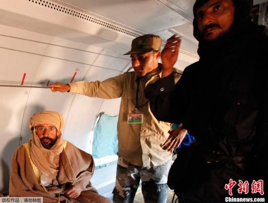 """11月19日,在利比亚的津坦,卡扎菲次子赛义夫・伊斯兰・卡扎菲(左一)在一架飞机里。利比亚""""全国过渡委员会""""(过渡委)军方19日在的黎波里宣布,执政当局在利比亚南部塞卜哈地区成功抓获卡扎菲次子赛义夫・伊斯兰・卡扎菲。"""