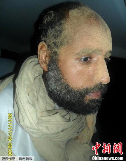 """这张来自利比亚""""二月十七日""""网站的图片显示,11月19日,卡扎菲次子赛义夫・伊斯兰・卡扎菲被送到津坦城。利比亚""""全国过渡委员会""""(过渡委)军方19日在的黎波里宣布,执政当局在利比亚南部塞卜哈地区成功抓获卡扎菲次子赛义夫・伊斯兰・卡扎菲。随后用一架运输机将其空运至津坦城。"""