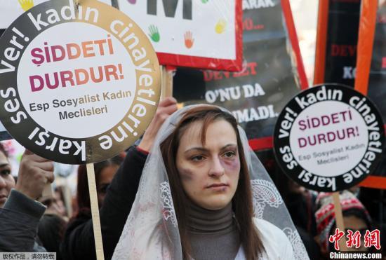 """材料图:一名土耳其妇打扮成遭到家暴后的形态上街抗议家庭暴力,她举着""""截至暴力止""""的牌子。"""