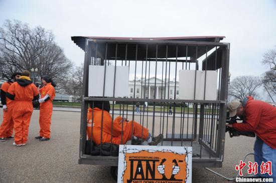数百名抗议者走上华盛顿街头进行抗议示威,并在白宫前集会,要求美国总统奥巴马尽快兑现当时竞选承诺关闭关塔那摩监狱。图为当日一名抗议者身穿橘色囚衣、戴着黑色头套装进铁笼子在白宫前抗议。发 吴庆才 摄