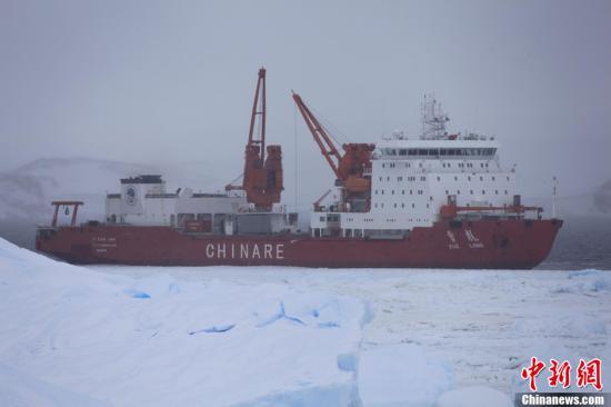 """2月17日下午,中国极地考察船""""雪龙""""号破冰营救""""黄河""""艇回船。2月13日晚,雪龙船上的""""黄河""""艇拖载着装满油料的驳船至中山站1公里外的丹凤岛岸边,将油料成功输送至中山站后。由于天气气温下降,海上浮冰冻结成片,没有破冰能力的""""黄河""""艇,其后几天在乱冰山和海上浮冰之间突围而没有成功。17日下午开始,""""雪龙""""号开至海上浮冰区边缘,成功破冰,为""""黄河""""艇在海上浮冰间开辟一条水道,""""黄河""""艇顺着水道成功回到雪龙船。记者 阮煜琳 摄"""