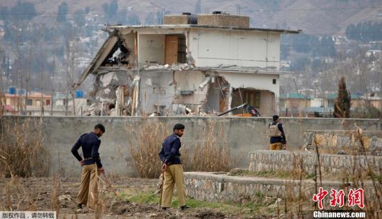 """资料图:巴基斯坦当局25日动用推土机,拆除位于阿伯塔巴德市的""""基地""""组织前领导人本·拉登生前最后的藏身住所。巴基斯坦方面没有就拆除这一建筑的原因做具体说明。不过,也有巴方官员透露,准备在该地修建公园。"""