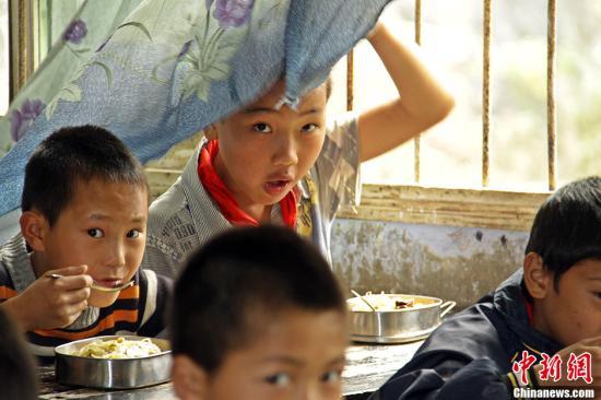 资料图:乡村小学学生食用营养午餐。/p中新社发 陈畅 摄