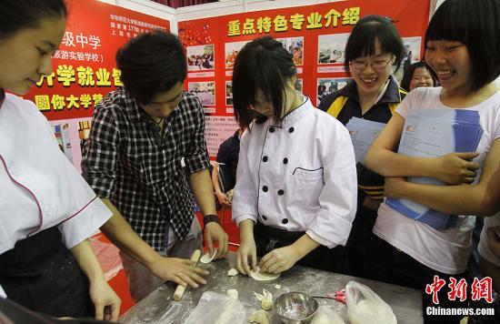 """5月4日,在2012年上海教育博览会DD职业教育专题展上,主办方特意为学生举办职业体验日,引导学生提前规划职业。那些""""工作岗位""""吸引了众多孩子前来争当""""职场人""""体验不同职业的魅力。中新社发 汤彦俊 摄"""