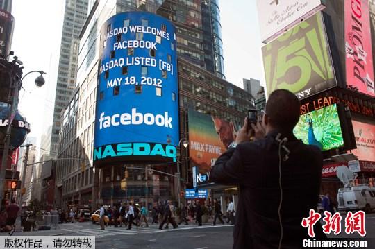 """资料图片:2012年5月18日,行人从美国纽约纳斯达克证券交易所外经过,电子显示屏上显示出""""脸书""""在纳斯达克上市的消息。"""
