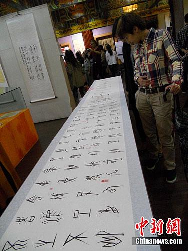 5月24日,重庆华岩寺展出由华岩寺方丈道坚大和尚历时1年多创作的120余幅甲骨文字画。其中不仅有充满禅味的偈语、佛家经典《心经》,还有一幅长约36米的《甲骨文字歌》。图为市民正在欣赏甲骨文书写的佛家经典《心经》。<a target='_blank' href='http://www.chinanews.com/'>中新社</a>发 韩璐 摄