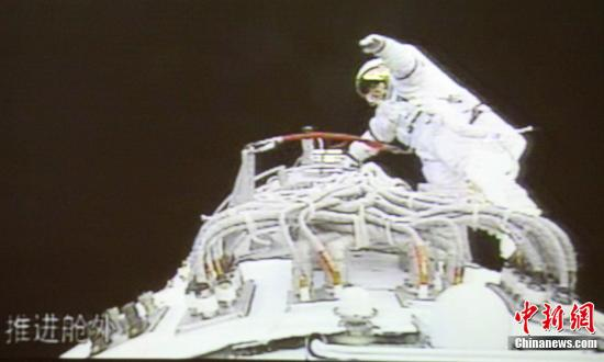 """北京时间2008年9月27日16:59,""""神舟七号""""航天员翟志刚成功出舱,实现中国历史上第一次太空行走。图为摄于北京航天飞控中心大屏幕的在太空中的翟志刚。(摄于电视屏幕)中新社发 齐彬 摄"""