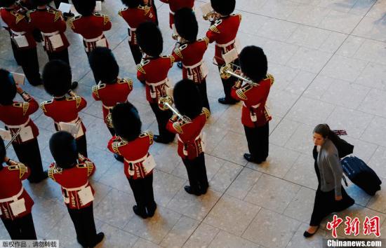 6月20日,伦敦希斯罗机场挂上12米宽的巨型五环迎接八方来宾。图为爱尔兰卫队在揭晓仪式上表演。