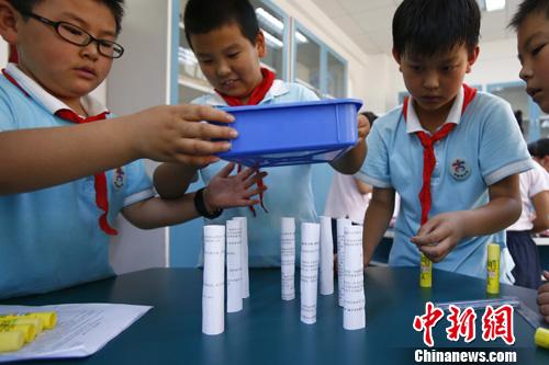 """近日,一堂以""""可持续教学模式""""为主线的科学课在北京海淀区中关村第二小学百旺校区展开,学生们以纸为支撑物,比赛谁制作的纸柱能承受更多瓶装水的压力。<a target='_blank' href='http://www.chinanews.com/'>中新社</a>发 富田 摄"""