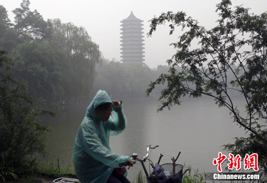 6月24日,一名学生披着雨衣骑过北大未名湖畔,当日北京从早上一直到傍晚都下起了中雨,加上能见度不足500米的雾气,对在端午节假期游玩的人们出行造成了不便。发 张浩 摄