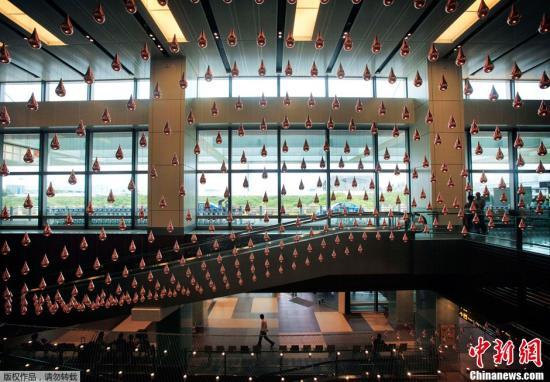 资料图片:2012年7月4日,新加坡樟宜国际机场,人们欣赏一个巨大的动力结构。