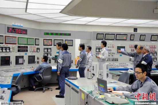 """2012年7月5日,在大饭核电站3号反应堆开始供电后,工作人员在日本大阪关西电力公司的中央电能输送指挥中心工作。日本关西电力公司大饭核电站3号反应堆5日开始供电,结束日本将近两个月的""""零核电""""状态。"""