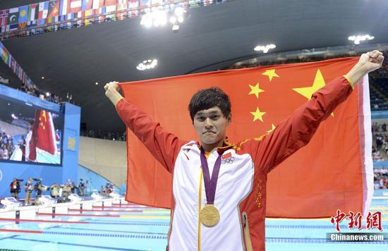 资料图:2012伦敦奥运会男子1500米自由泳决赛,中国选手孙杨以14分31秒02的成绩夺得冠军,这也是中国代表团本届奥运会上取得的第24枚金牌。图为孙杨披国旗庆祝夺冠。记者 廖攀 摄