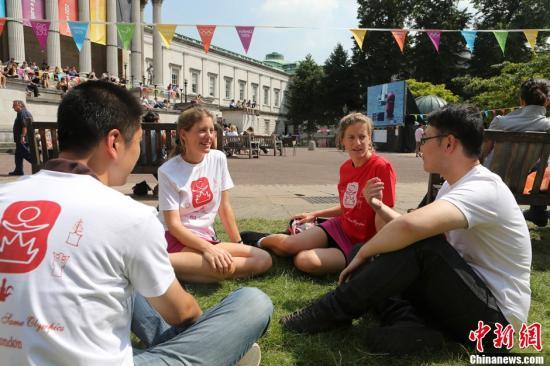 资料图片:在奥运会期间的伦敦街头,一批印满神秘字符的T恤引起人们的关注。据一名中国留学生介绍,T恤上面的字符源自山东莒县,是迄今为止中国发现的最古老的象形文字。奥运不但是一个各国体育竞技盛会,更是一个世界文明交融的舞台。中新社发 钟新摄