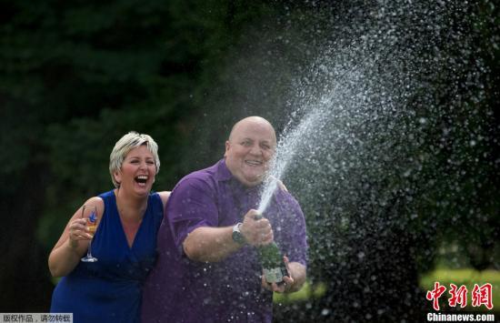 """资料图:当地时间2012年8月14日,英国哈特菲尔德希斯,""""欧洲百万乐透""""彩票开出巨奖,一对英国夫妇中了1.9亿欧元(约1.49亿英镑)的彩票奖。图为中奖夫妇中奖后庆祝。"""