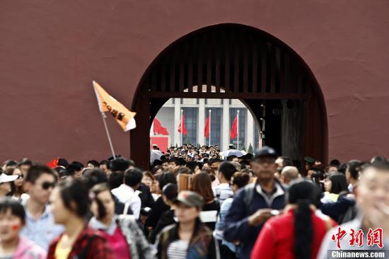 10月3日,北京天安门广场游客众多。10月2日和3日成为了今年国庆旅游的首个高峰期。中新社发 张浩 摄