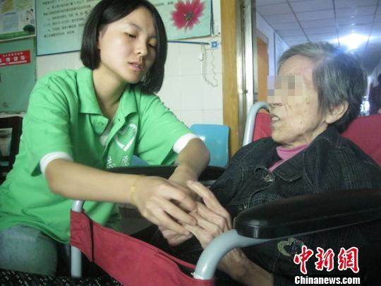 资料图:一名志愿者为患老年痴呆症的老人按摩手指。刘柱 摄