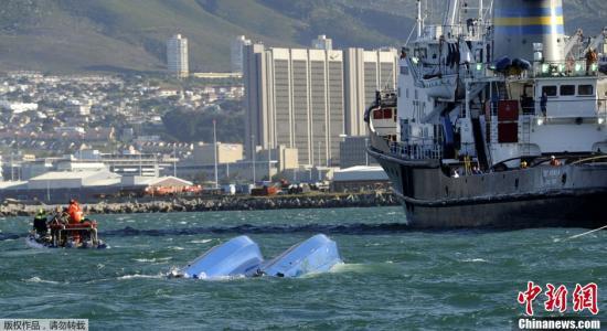 资料图片:当地时间10月13日,南非开普敦胡特港湾,一艘游客观光船遭遇大风,在小羚羊岛附近翻船,救援人员在失事附近海域和码头上抢救遇难船只上的幸存者。