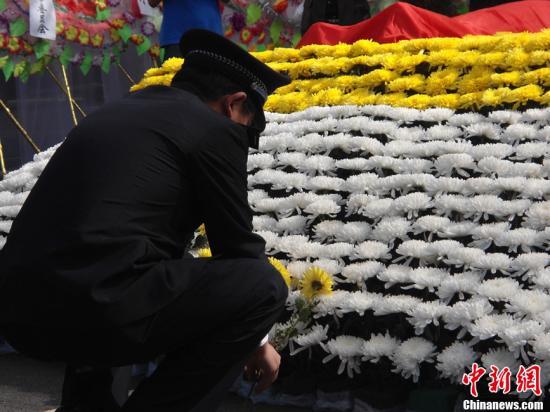 原料图:就义民警同事献花寄悲思。中新社发 顾一航 摄
