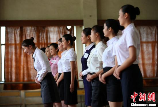 """10月19日,上海,穿着漂亮的制服,翱翔在蓝天之上……不少女孩的心中都有这样一个""""空姐梦""""。东方航空公司航沪面向华东六省一市统一招收800名空中乘务员,在考点上海仙霞路上的上海工程技术学院内的室内体育馆进行,应聘者中既有在校大学生也有曾经的""""高姐"""";而为了圆自己的空姐梦,有应聘者全家出动""""陪考"""",也有应聘者千里迢迢从外省赶来。图为面试中,考生做自我介绍和走路姿态。图片来源:CFP视觉中国"""