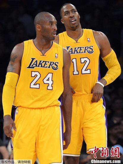 """资料图:2012年NBA季前赛,湖人队主场92-99萨克拉门托国王队,遭遇新赛季季前赛6连败。这是全明星中锋""""魔兽""""霍华德第一次为湖人披挂上阵。图为湖人球员霍华德(右)与科比。"""