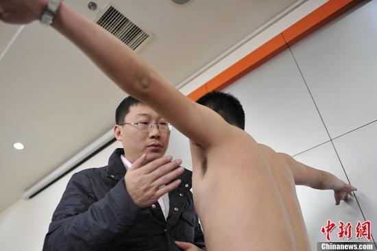 11月3日,在山西太原,航空公司招聘人员在检查应聘男子腋下有无狐臭。当日,中国海南航空公司与东方航空公司在山西太原举行飞行员招募活动,吸引了众多志在飞翔蓝天的90后大学生前来报名。/p中新社发 韦亮 摄