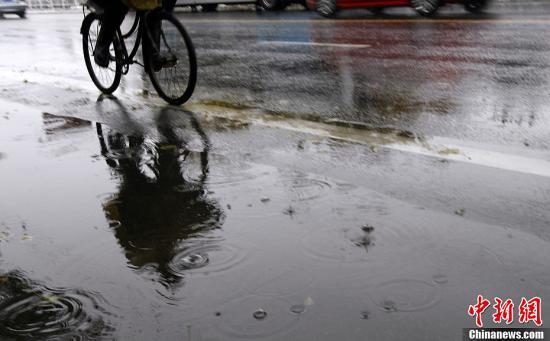 11月4日,一位行人在雨雪中骑车。当日6时,中央气象台发布暴雪橙色预警和寒潮蓝色预警,同时,北京、河北于4日早间相继发布暴雪红色预警。北京雨雪将持续40小时,雪量或超历史极值。中新社发 李慧思 摄