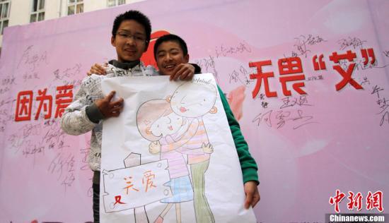 """11月29日,安徽省合肥市五里墩街道组织学生在校园开展关""""艾""""活动。图为学生相互拥抱,用行动鼓励社会多关爱HIV感染者。<a target='_blank' href='http://www.chinanews.com/'>中新社</a>发 韩苏原 摄"""