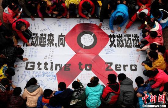 资料图:市民在抗艾滋病宣言上签名。程千俊 摄 图片来源:CFP视觉中国