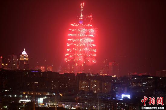 """2012年12月31日深夜,台北101大楼施放以""""火鸟""""为设计概念、以""""舞动未来""""为主题的烟火,首次采法式浪漫风格,耗资3000万新台币,持续188秒。加上附近的2013年台北跨年晚会,预估有80万民众和游客,跟着璀璨烟火秀一起在倒数声中迎来新的一年。中新社发 董会峰 摄"""