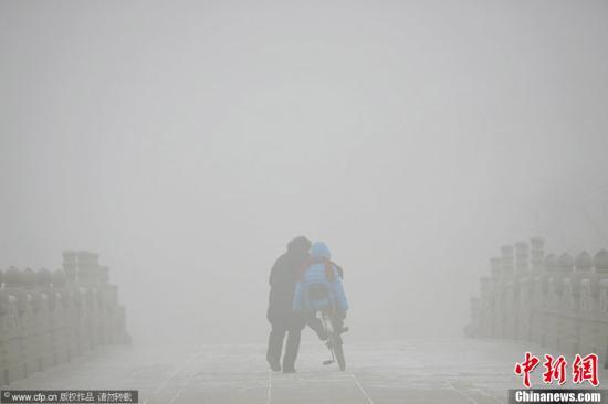 1月12日,浓雾封锁河北已进入第9天,雾情丝毫未退且正升级。自2013年1月4日开始,河北5个城市空气质量上升到5级重度污染以上水平。图为1月11日,河北省石家庄市,一位家长推在自己的孩子在水上公园的石拱桥上艰难前行。贺志泉 摄 图片来源:CFP视觉中国